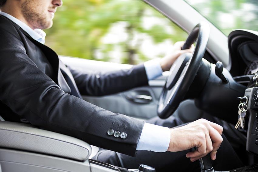 Подлокотник в автомобили. На фото мужчина управляет авто.